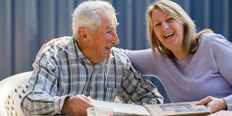 Colleen Inglis, laughing with elderly man, looking at photos, photo album, Care Worker story, HammondCare, home care,